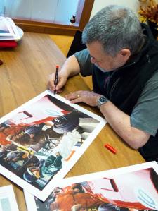 Alberto nel suo studio mentre autografa le sue opere