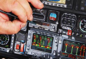 La mano ferma e sicura di Ercole Furia mentre rifinisce i dettagli della strumentazione di un cockpit aeronautico