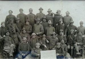 Una foto storica dove 29 Mascabroni, il reparto di indomiti Alpini del capitano Sala, posa davanti ad un cartello che li ricorda come i reduci della Cma Undici e del passo della Sentinella