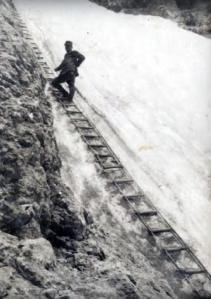 Un Alpino posizionato su una delle tante scale in corda posizionate nei punti più scoscesi e assicurati alle pareti con dei fittoni o chiodi ancorati nella roccia alla cui estremità c'era un anello